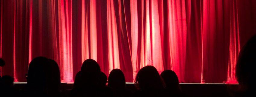 Rood theaterdoek met publiek ervoor