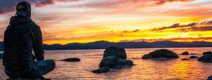 Rust: iemand kijkt uit over de zonsondergang en de zee